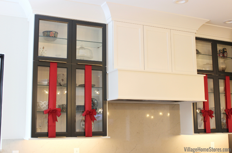 White kitchen cabinets with red ribbon on doors for holiday decorating