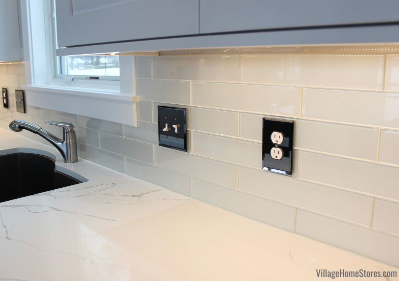 """3"""" x 14"""" long subway tile backslash in kitchen with mirrored outlet and switch covers."""