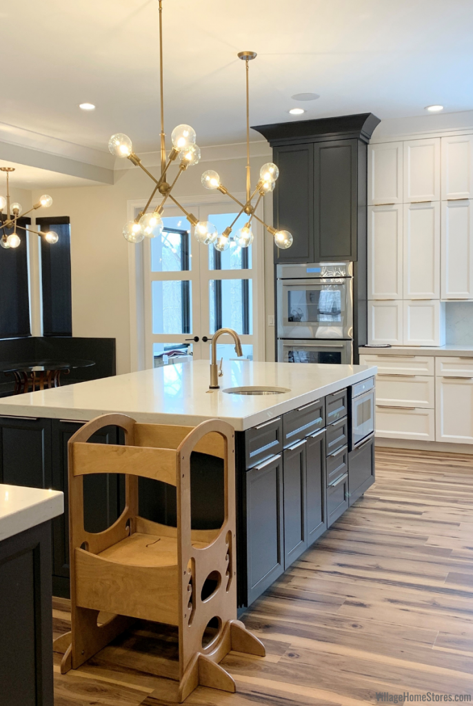 Modern kids stepstool up at kitchen island. White and gray painted kitchen with modern cabinetry and sputnik style gold island lighting.