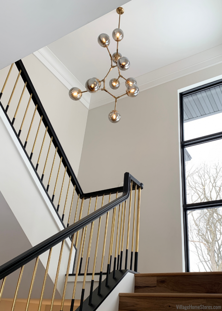 Gold and Black stairwell in a modern home with unique sculptural light fixture named Synapse from ELK Home Lighting.