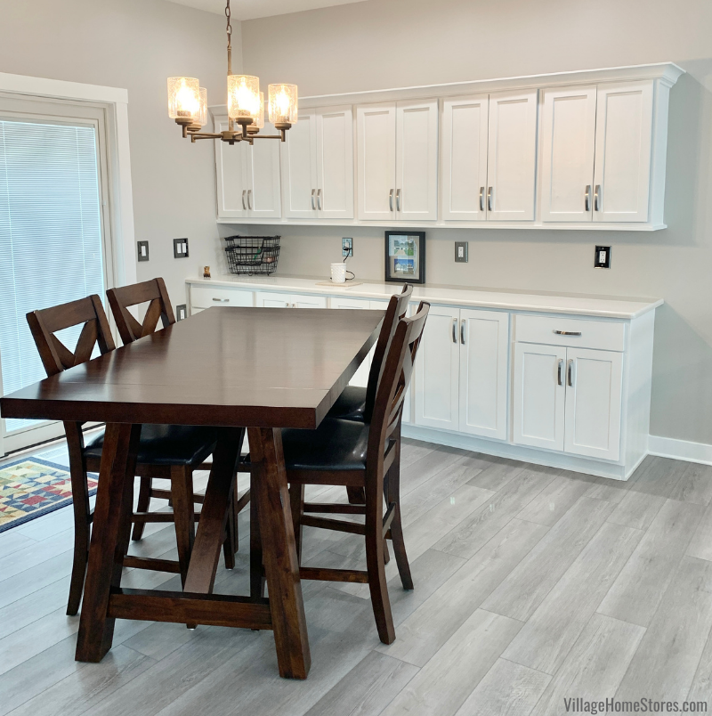 Great room kitchen with serving area cabinetry on back wall near tall height dining table.