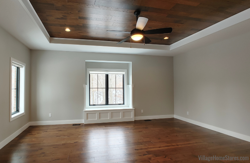 Wood flooring on floors and tray ceiling of a bedroom.