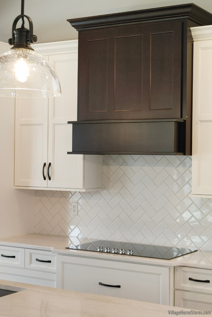 Birch Java wood range hood above KitchenAid electric cooktop. Arctic White subway tile installed as backsplash with Cambria Quartz Ironsbridge countertops. Kitchen design and materials by Village Home Stores for Hazelwood Homes of the Quad Cities.