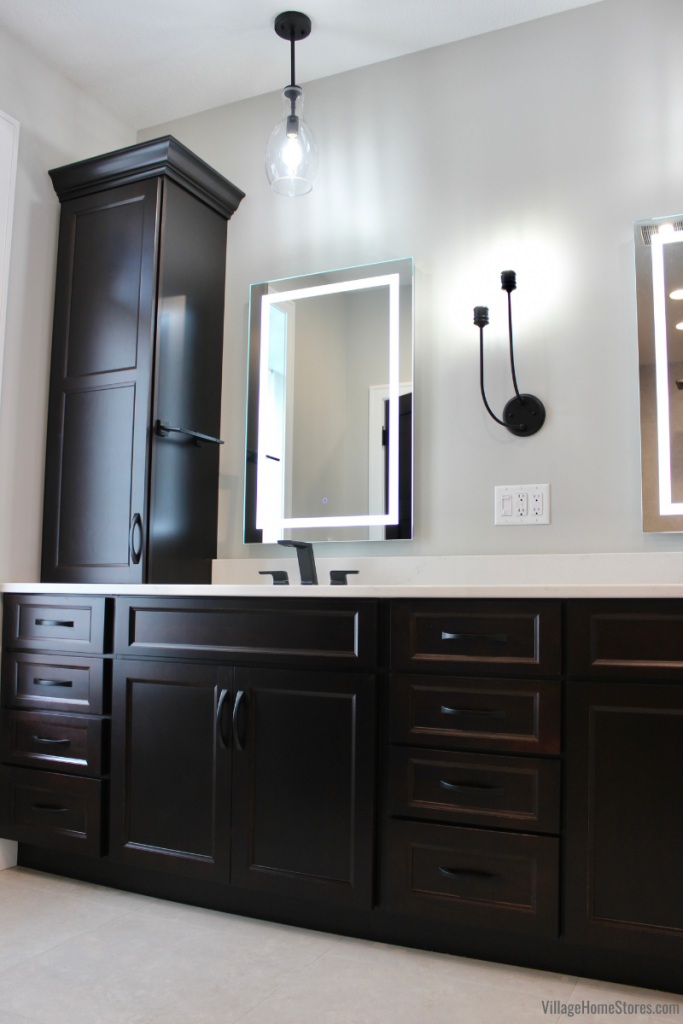 Dark Java stained bathroom cabinets with linen tower on counter and LED mirror.