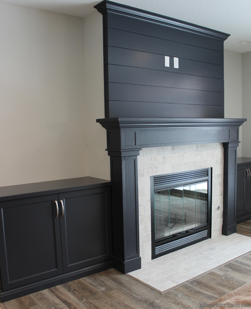 charcoal blue painted cabinets paneling and mantle surrounding a fireplace.