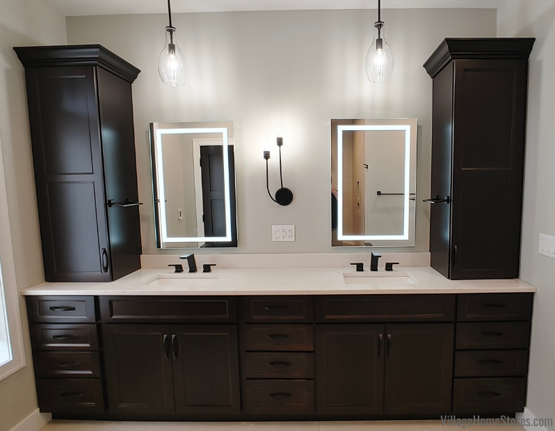 Two vanity sink setup with LED mirrors and dark cabinets.