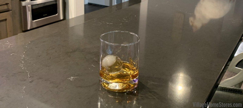 Glass of whiskey with ice ball in home bar in Bettendorf Iowa with black Cambria Quartz counters in the Charlestown design.