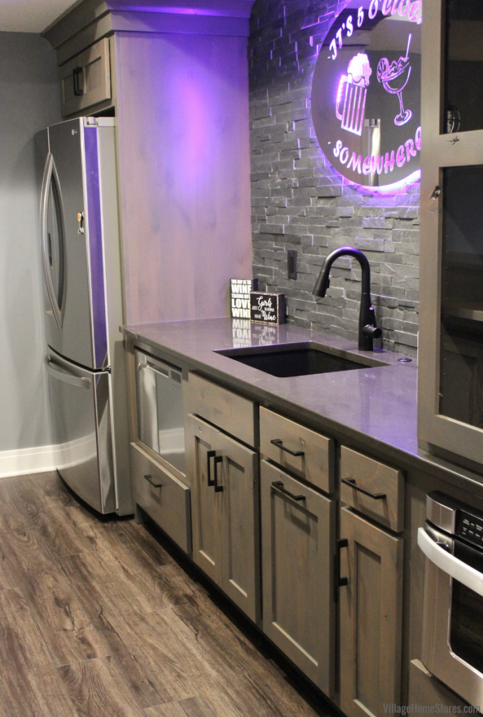 Bar cabinets and quartz counters in a Bettendorf Iowa home with black slate ledger stone on the wall and LED bar sign.