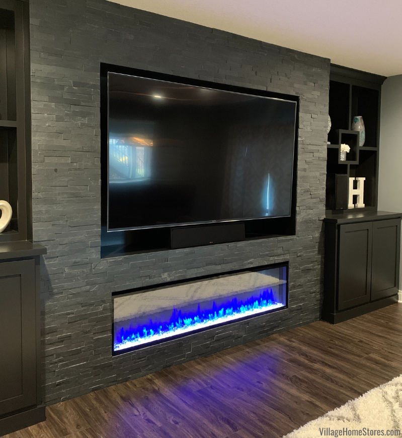 Black slate ledger stone surrounding a lower level fireplace and tv area.