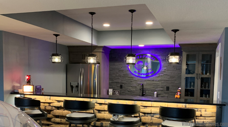 Home bar in Bettendorf Iowa with caged Quorum Galveston pendant lighting hung from varied height ceiling.