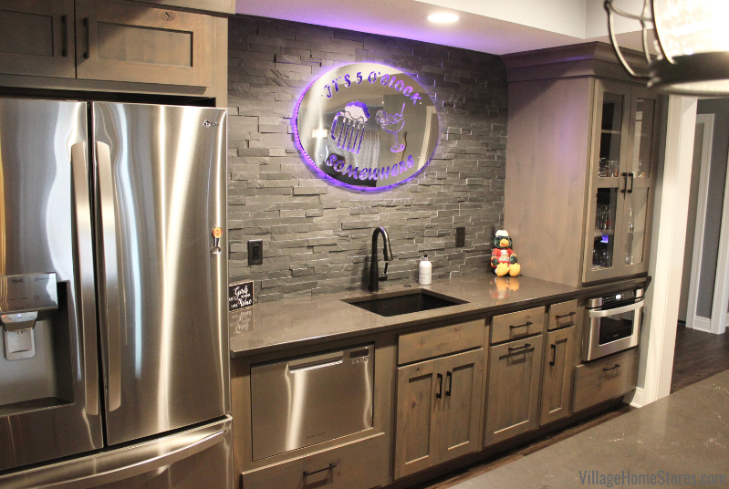 Home bar with Koch Cabinetry Knotty Alder cabinets and Cambira Quartz in Black Charlestown design