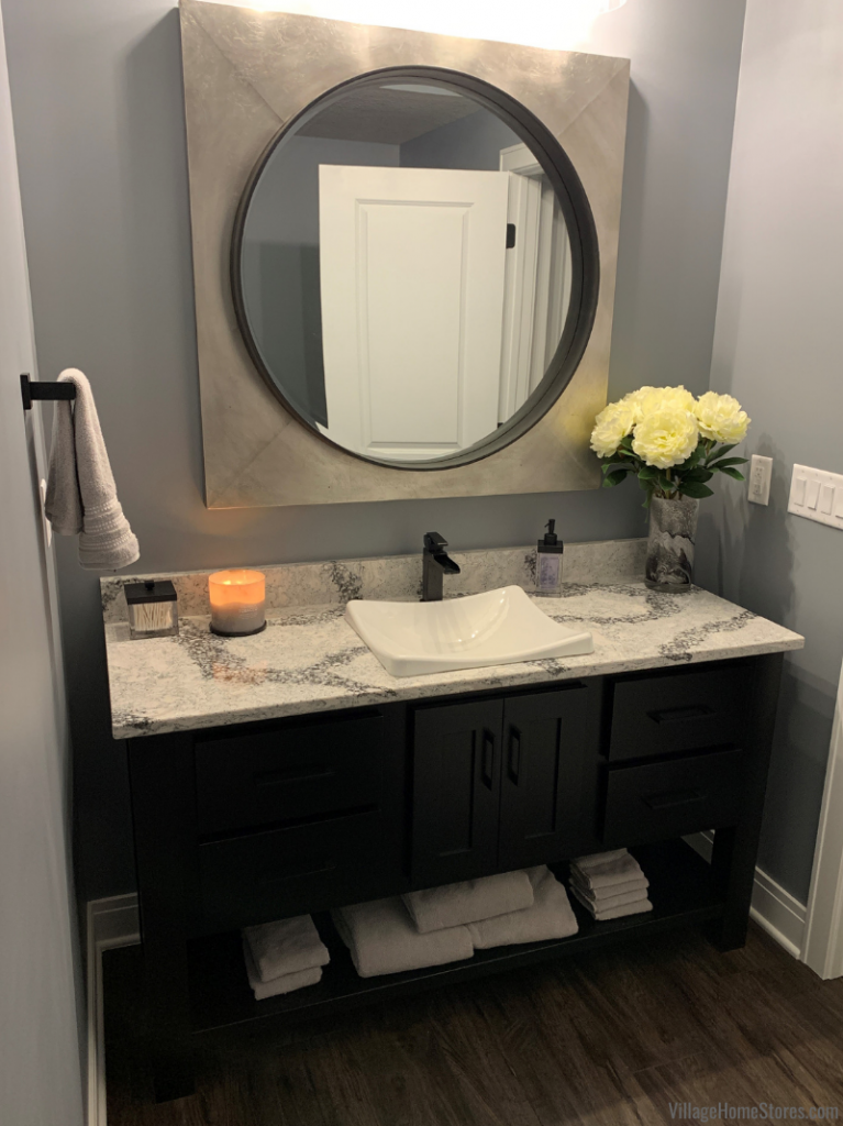 Cambria Quartz vanity top in the Seagrove design installed on a furniture vanity in painted black. Guest bath in a Bettendorf, Iowa home with design and materials by Village Home Stores.