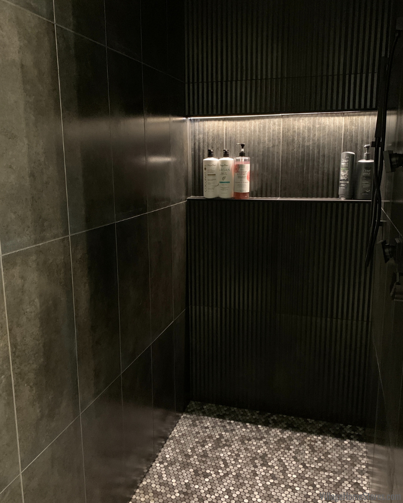 Shower with large tile in a Bettendorf Iowa home. Molten series 12 x 24 inch tiles in Nero Raku color with LED lit shelf.