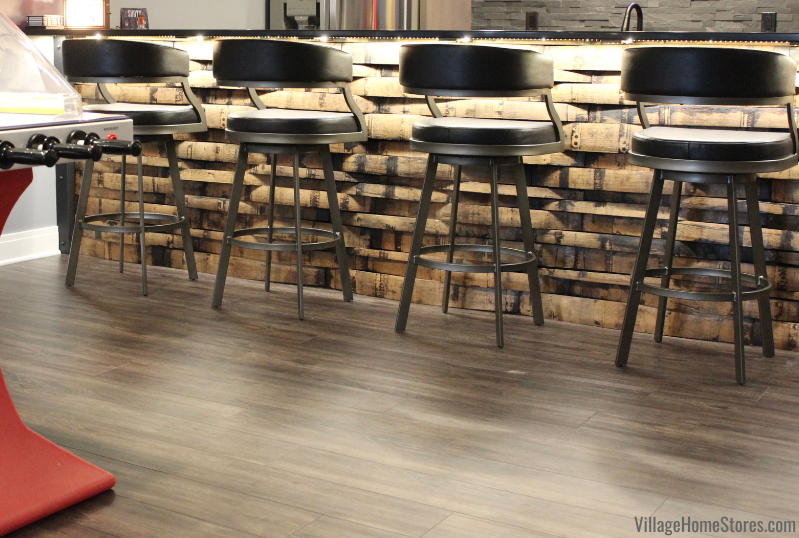 Gray Luxury Vinyl Plank flooring in a game room and home bar in Bettendorf Iowa. Adventure II series in Rain Forrest color. Flooring by Village Home Stores