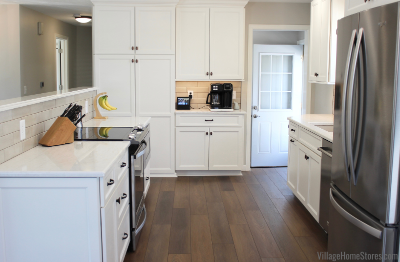 Ivory white painted cabinet kitchen with stainless appliances and medium oak vinyl plank flooring.