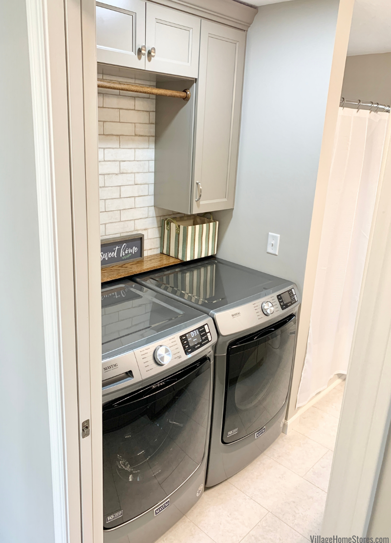 Laundry room bathroom design with Maytag front load laundry and Koch Cabinetry in Bristol door and Taupe painted finish.
