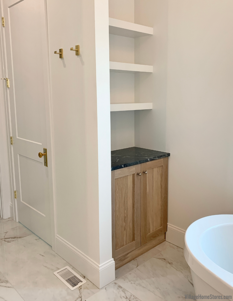 Oak cabinet in bathroom with open floating shelves above. Cabinetry and tile by Village Home Stores for Hazelwood Homes.