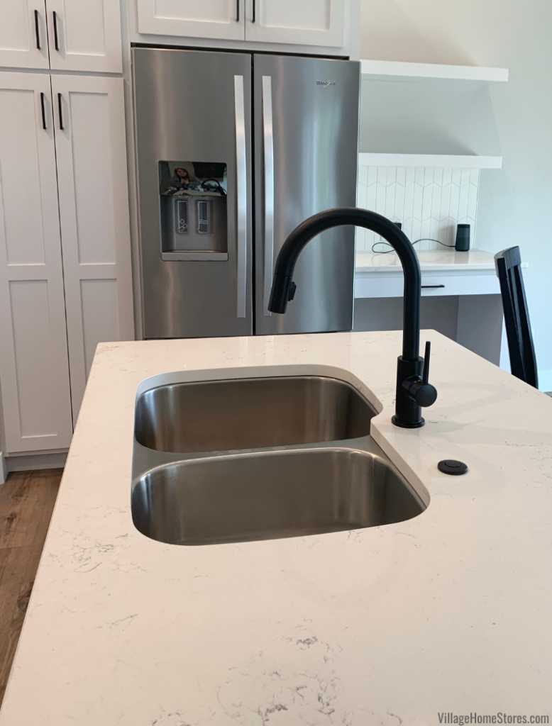 MSI Carrara Marmi Quartz counters with a stainless steel undermount sink and matter black kitchen faucet.