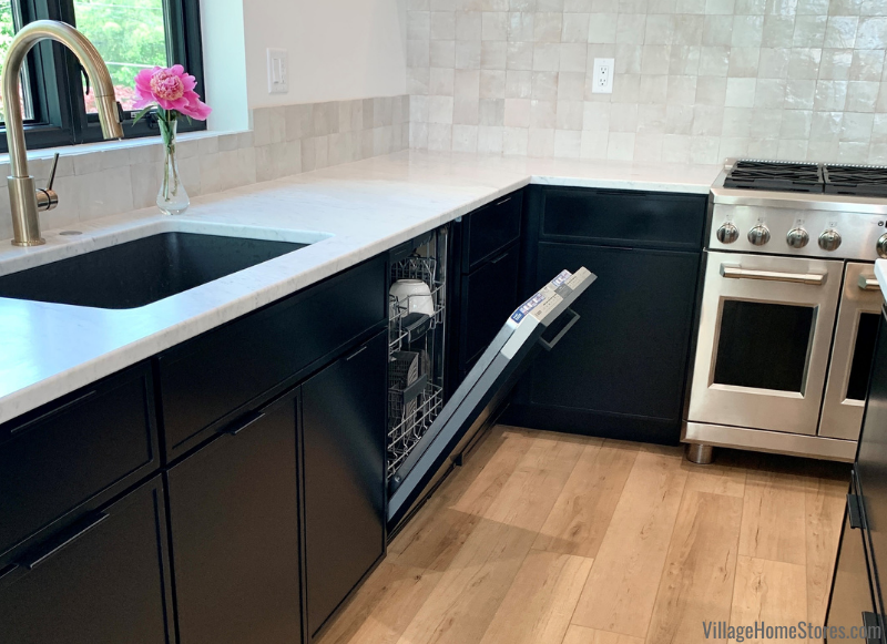 Dura Supreme dishwasher cabinet door in Reese door, painted black finish. Kitchen cabinetry and COREtec flooring from Village Home Stores.