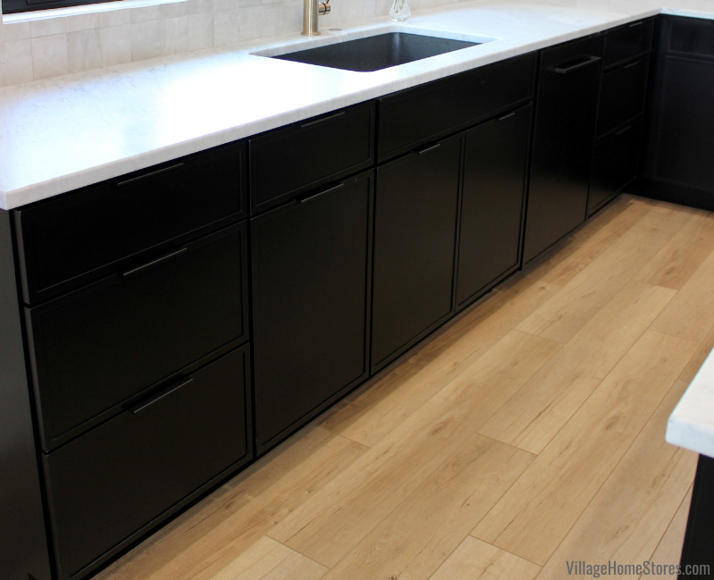 Dura Supreme skinny shaker Reese door in painted black finish with Edgefield hardware. Kitchen cabinetry and COREtec flooring from Village Home Stores.