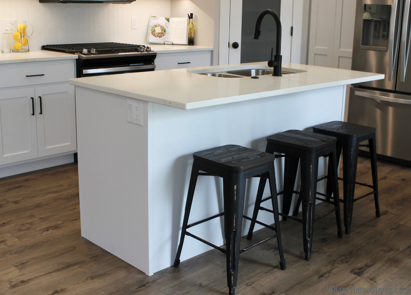 Painted white Koch Express cabinet kitchen with seating at island.
