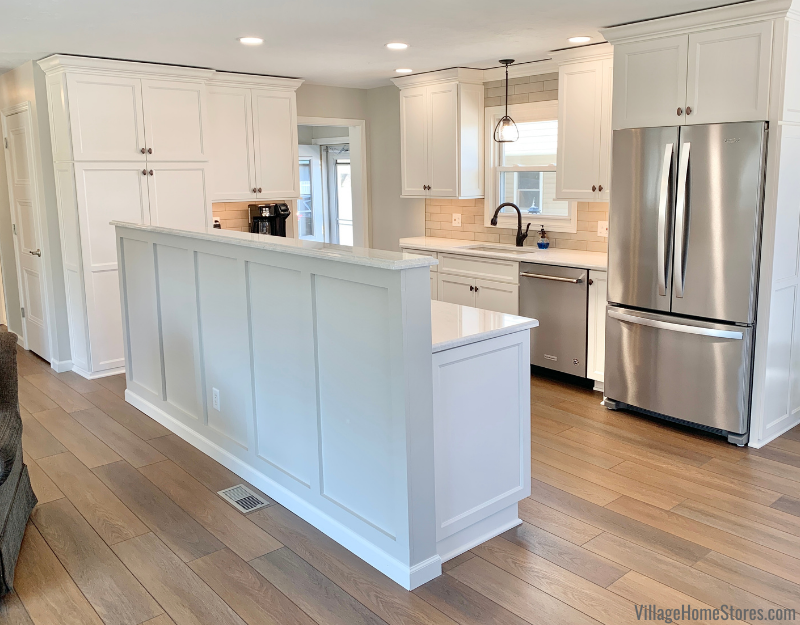 """Kitchen remodel in Geneseo, Illinois featuring Koch cabinetry in the """"Bristol"""" door and painted """"Ivory"""" finish with Cambria Quartz counters in the Ironsbridge design. Flooring is from our best-selling COREtec luxury vinyl plank line in the """"Lanier Oak"""" color."""