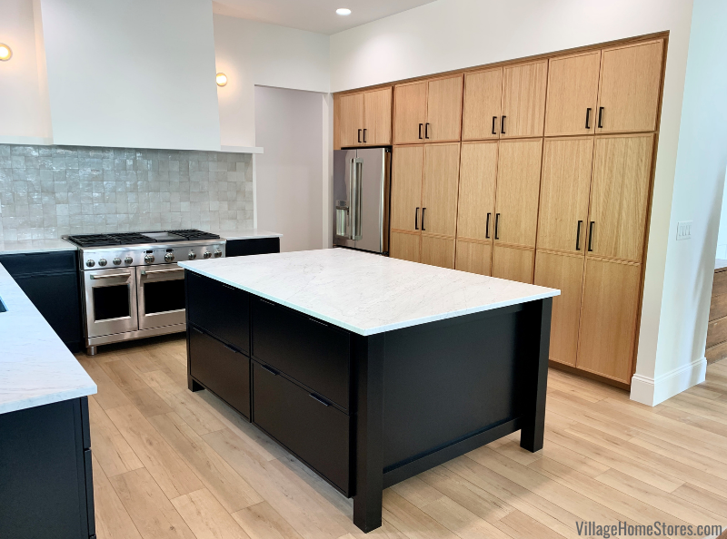 Minimalist kitchen design with combination of matte black and natural oak skinny shaker door kitchen cabinetry from Village Home Stores for Hazelwood Homes of the Quad Cities.