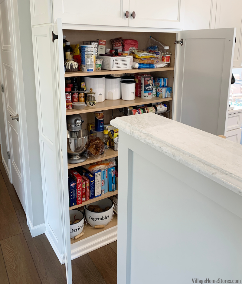 Tall pantry cabinet with shelves in kitchen design. Koch Cabinetry in Bristol door and Ivory White finish.