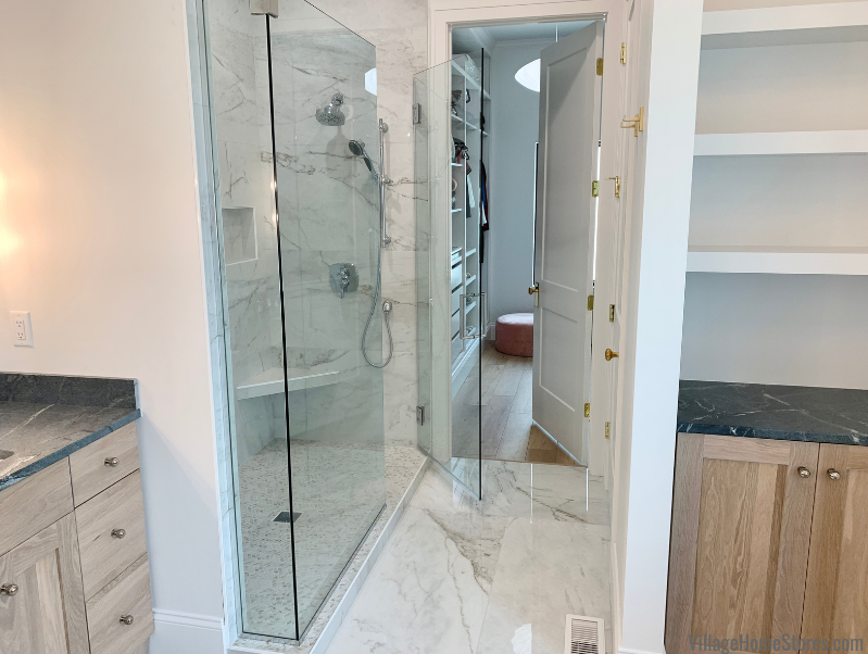 Tiled shower in primary bath of a new Moline, IL home. Cabinetry and tile by Village Home Stores for Hazelwood Homes.