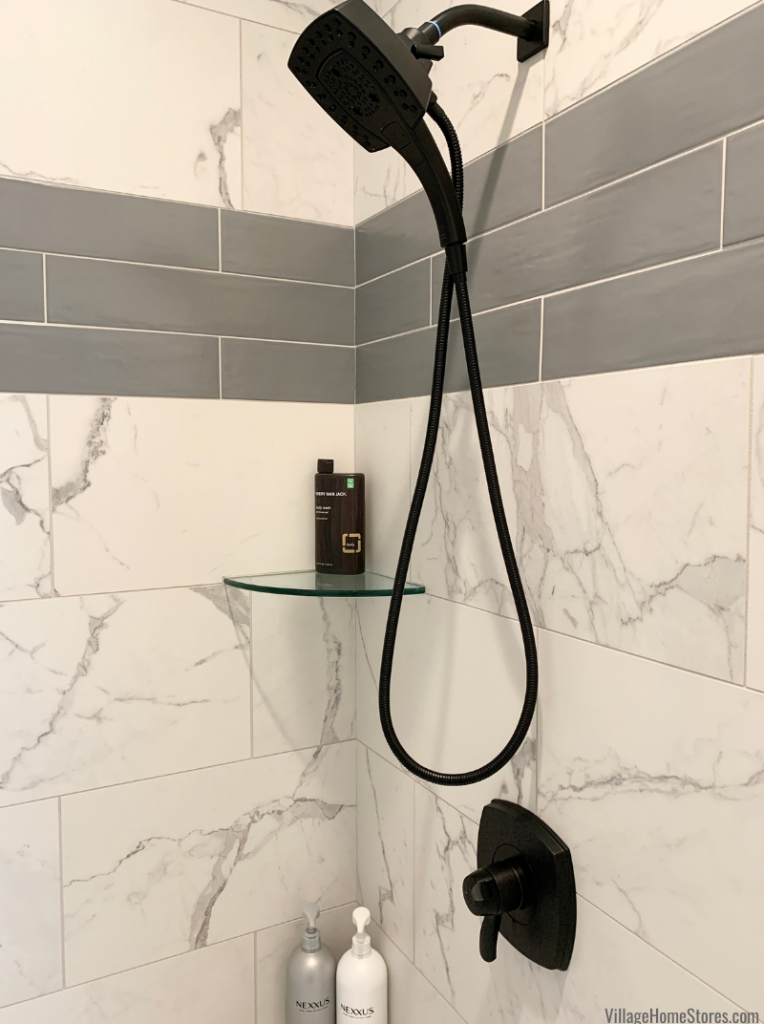 Stripe of long, gray accent tiles in a shower with corner glass shelf.