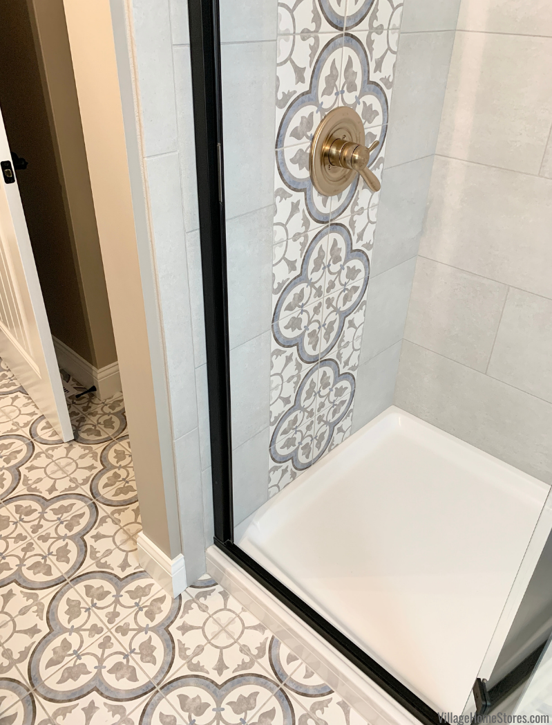 Black framed glass shower door in tiled bathroom with painted tile accents.