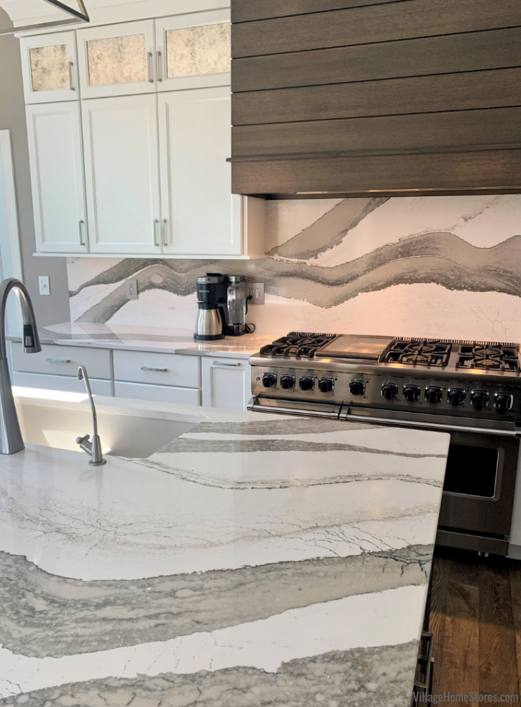 Cambria Quartz counters and full-height backsplash in the Skara Brae design paired with white and gray stain kitchen cabinetry.