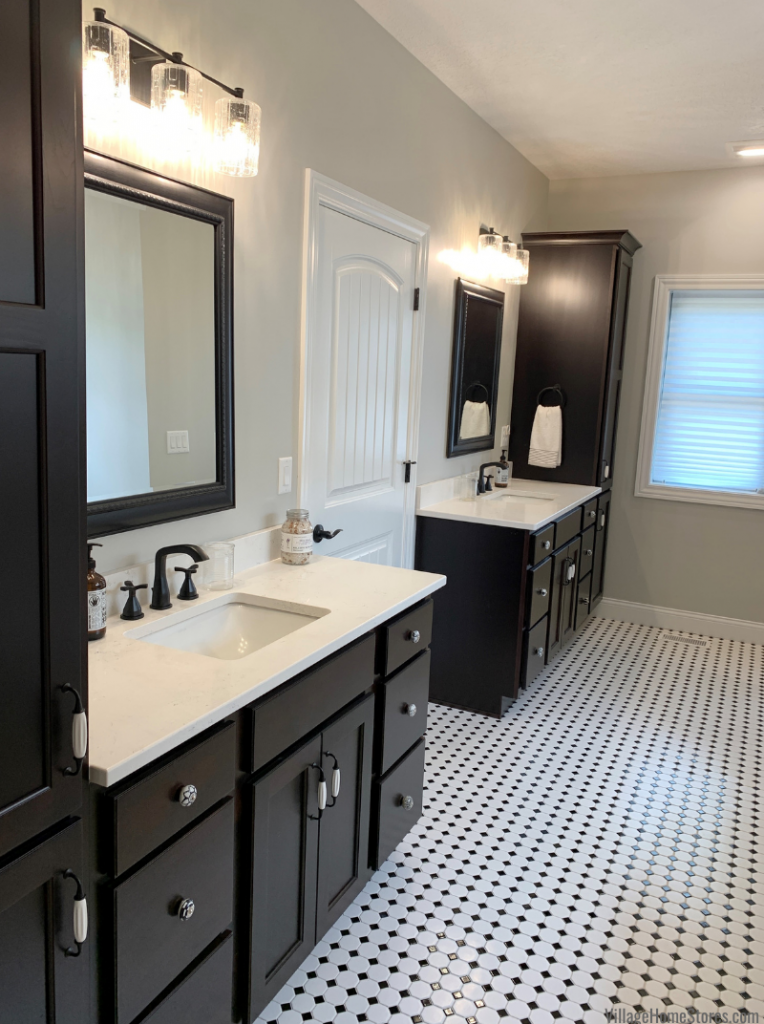 Java stained bathroom cabinetry with split vanities on black and white octagon with dot tiled floor.