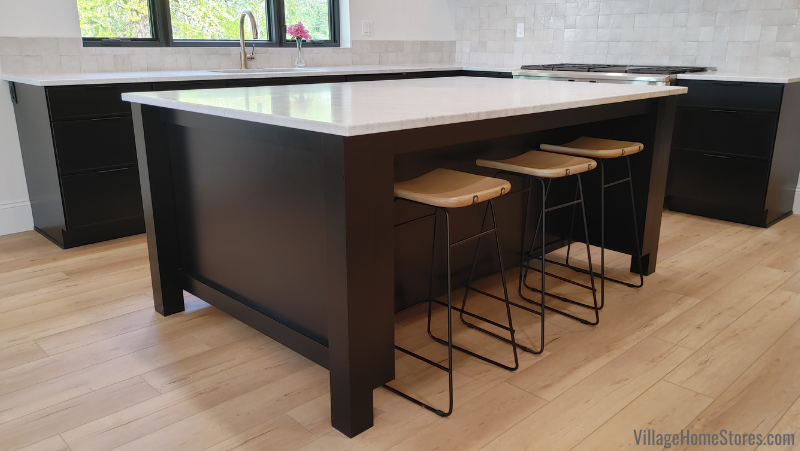 Kitchen island cabinets with overhang for seating in painted black finish. Dura Supreme cabinetry from Village Home Stores in a Moline Illinois home.