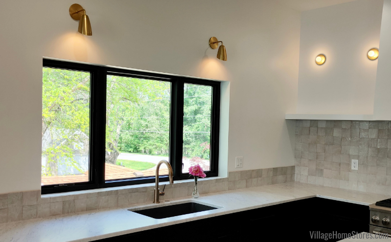Hudson Valley Mitzi aged brass sconces in a Quad Cities kitchen. Lighting and cabinetry from Village Home Stores for Hazelwood Homes.