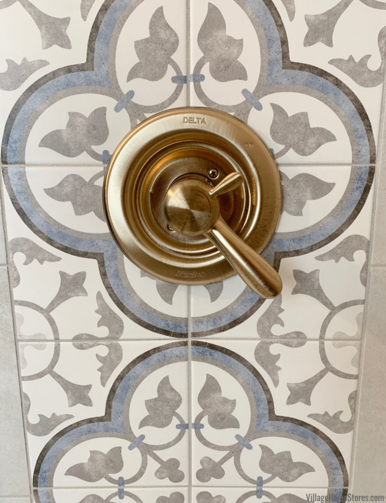 Brass shower controls on a gray and blue painted tile accent area in a shower.