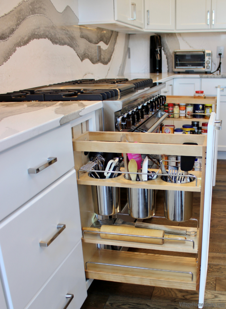 Utensil organizer pullout cabinet with bins and shelves in a custom Amish-built kitchen in Bettendorf, Iowa from Village Home Stores.