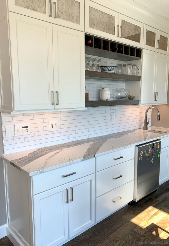 Wet bar in kitchen with white painted cabinets, long subway tile, and Cambria quartz counters.