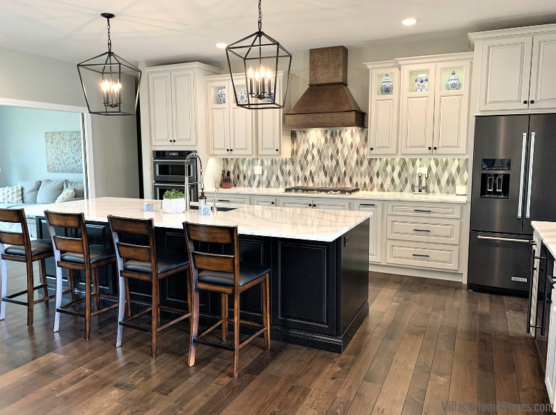 """Quad Cities area kitchen with Koch """"Oyster"""" painted kitchen, dark stained island, and Cambria Brittanicca quartz tops. Two lantern-shaped pendants hang above kitchen island."""