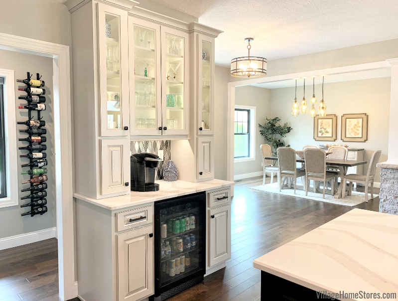 Dry bar design in kitchen with beverage cooler and glass door cabinets.