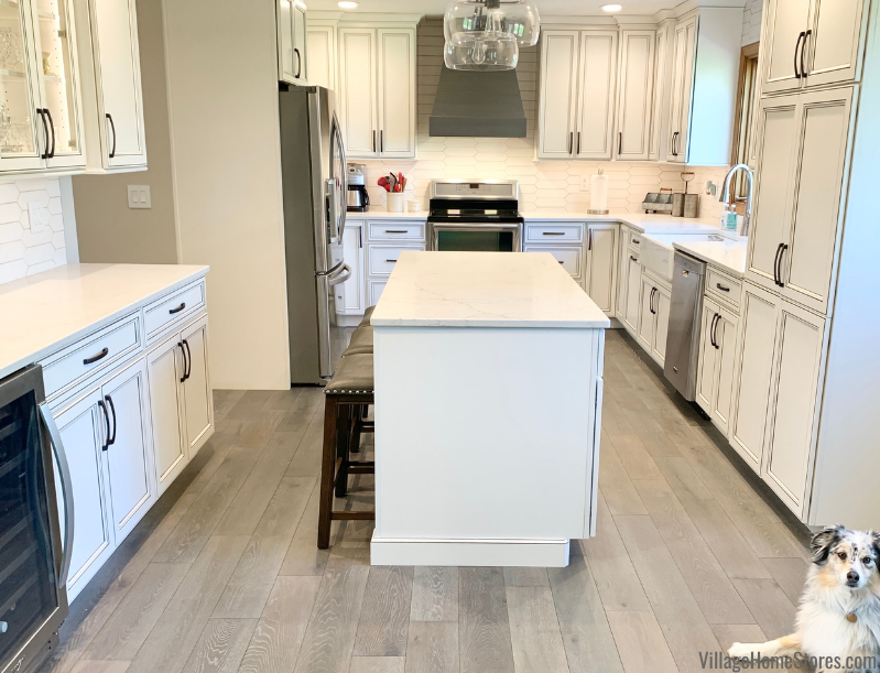 Kitchen remodel in a Geneseo, Illinois by Village Home Stores with center island and ivory painted cabinetry.