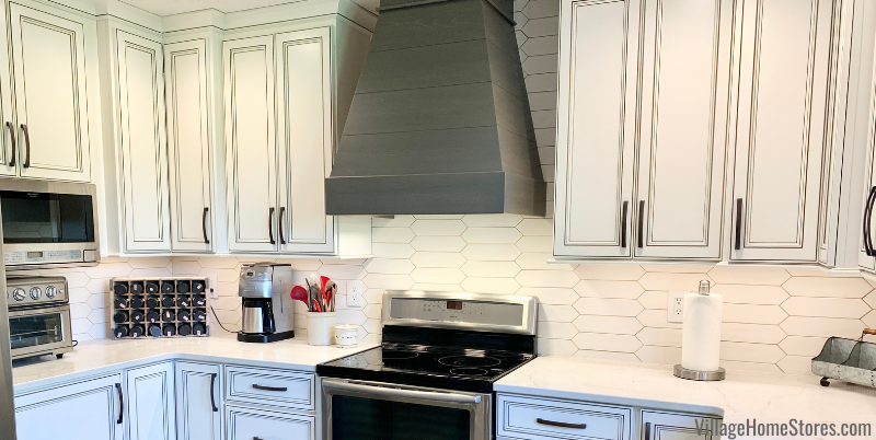 Kitchen remodel with crayon shaped tile backsplash and ivory painted Koch cabinetry by Village Home Stores.
