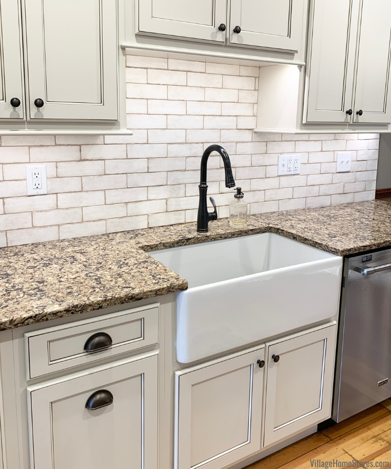 Farm sink installed with Cambria Quartz counters and our best-selling Vestige backsplash tile. Design and full remodel by Village Home Stores.