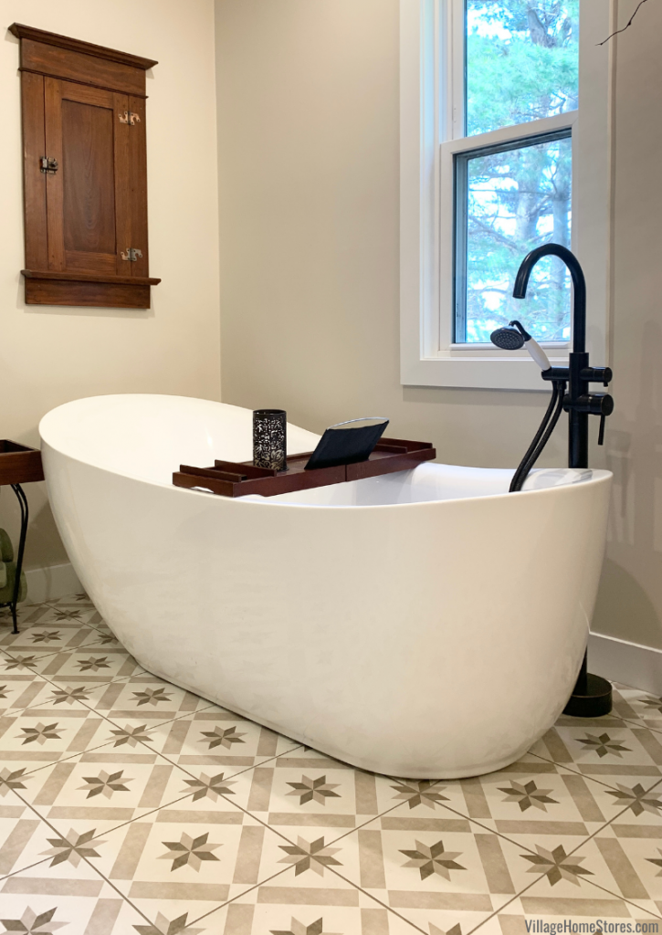 """Modern tub installed on farmhouse painted tile floors. Memoir series tile in """"Star Griege"""" color by Village Home Stores."""