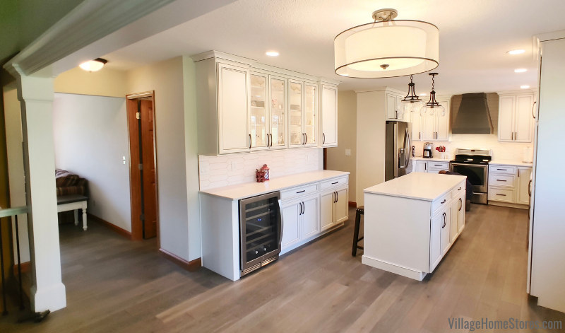 Kitchen remodel by Village Home Stores with wall removed and updated flooring, cabinets, and countertops.