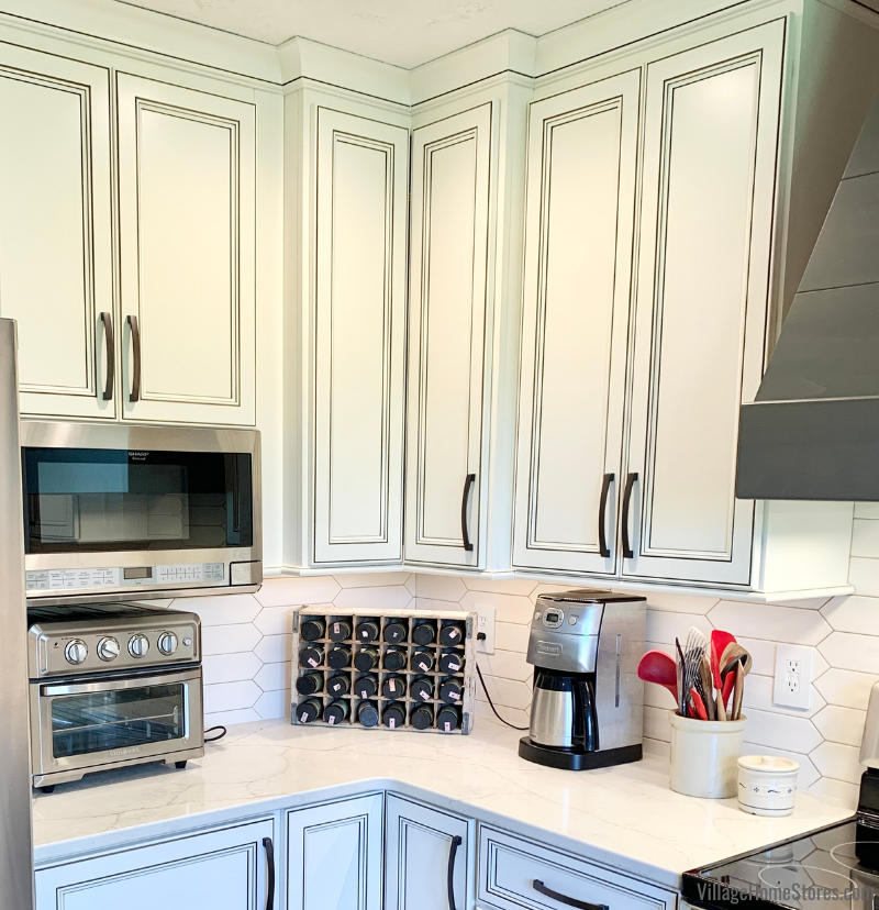 Over the counter microwave and Ivory painted cabinets to ceiling with crown molding.