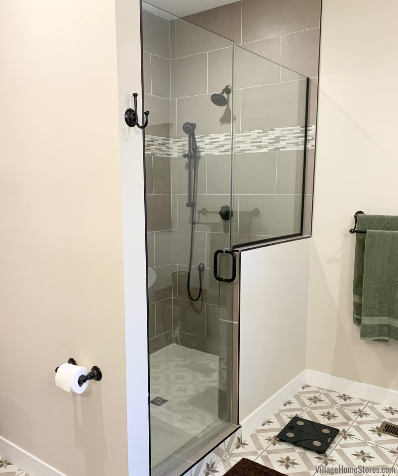 Tiled shower with half wall and glass door entry in a rural Illinois bathroom remodeled by Village Home Stores.