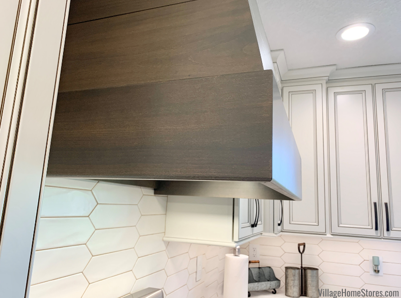 Wood range hood in Rustic Beech and Driftwood stain. Kitchen design and remodel by Village Home Stores.